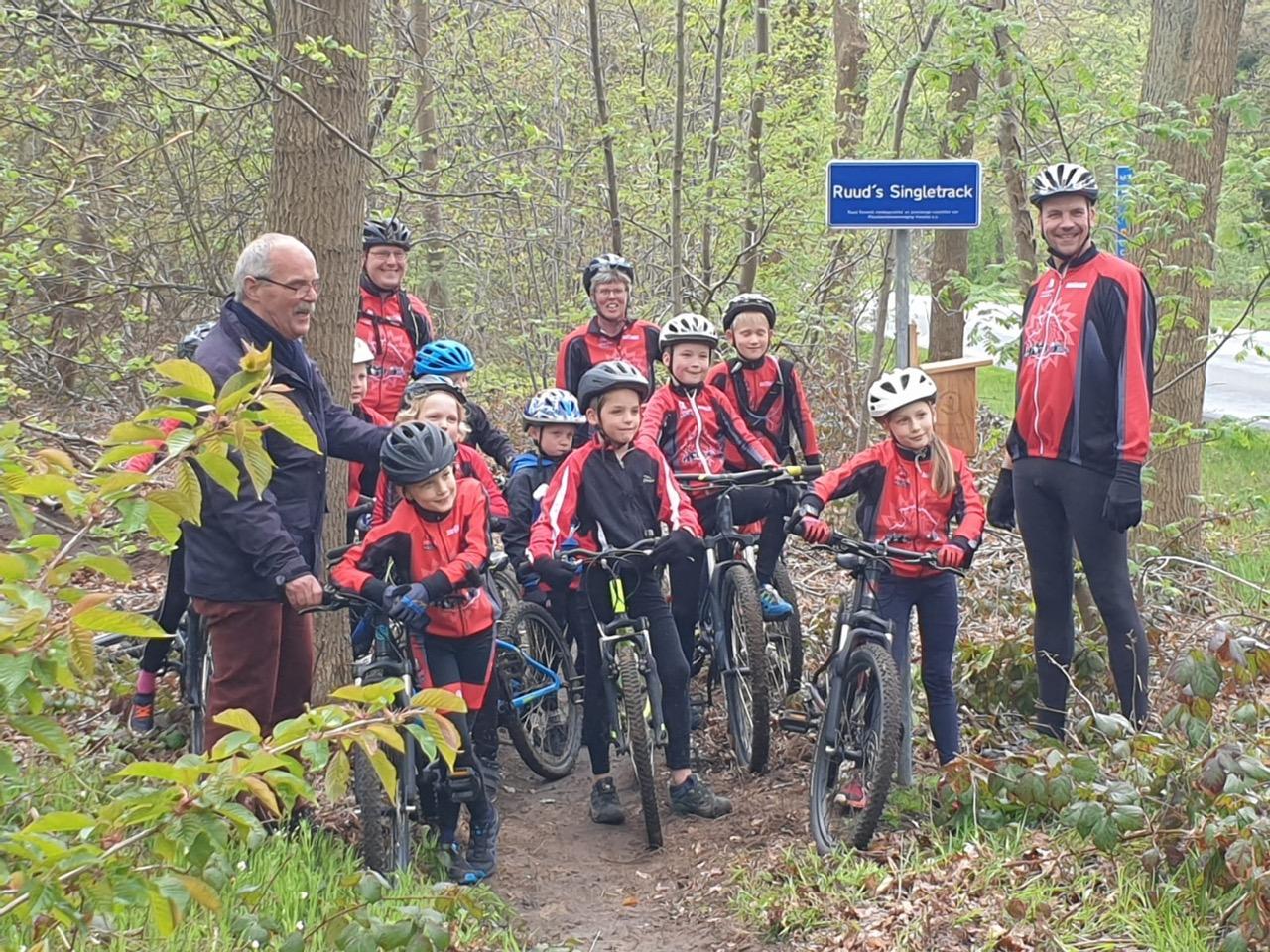 Ruud poseert samen met leden van de mountainbikevereniging bij zijn naambordje (Foto Maurice Smeenk)
